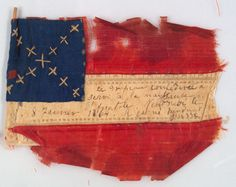 """Confederate silk bible flag, 1864. This miniature, hand-stiched flag commemorates a child's birth with an inscription in French: """"This confederate flag was present at the birth of Anatole. Friday, January 8, 1864. He was born during the war."""" The Historic New Orleans Collection, gift of Clyde Cucullu."""