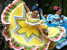 Dancers wearing bright colored dresses celebrating the Mexican holiday Cinco de Mayo. Here's a list of popular songs for this Mexican holiday.    http://www.bestdjforum.com/content.php?314-Cinco-de-Mayo-Music-Best-Songs-For-A-Fiesta