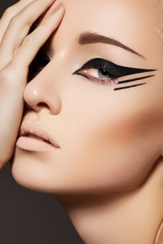This is some creative eyeliner, it involves a simple bold wing eyeliner and then 2 lines underneath. This would most likely be done with liquid liner, for precision and control.