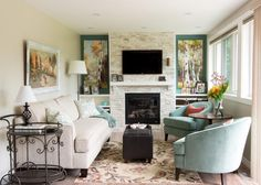 As seen on HGTV's hit show Love it or List it, this beautiful country chic living room includes muted tones of turquoise and white to compliment the tones of nature present in the artwork on the walls. The long row of windows brings in an abundance of natural light, while the floral rug and the fresh flowers help to further bring the outdoor into this comfortable living room.