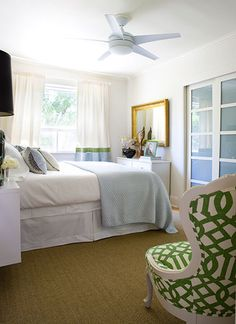 natural sisal rug mixed with bright green chair, white linens, pale blue quilt, two-tone curtains drapes, modern fan, glass door, bed skirt, bedroom.