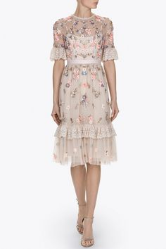 The Ditsy Scatter Dress has a flattering, fitted bodice with a fuller tulle skirt. The bodice fabrication is semi sheer tulle with an integrated camisole slip lining, finishing with our signature grosgrain trim at the waistband. Prairie inspired ruffle trims are featured on the sleeve and lower skirt in delicately embroidered tulle with lace inspired motifs. The Ditsy Scatter artwork is inspired by vintage ditsy fabric prints with pretty bunches of flowers. These are depicted in soft pastels…