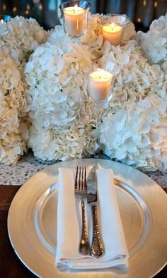The head table will have different heights of floating candles in tall votive holders and mercury glass votives surrounded by a cloud of white hydrangeas running the length of the table.