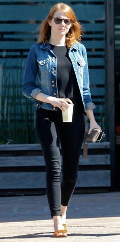 Snapped out and about in Los Angeles, Emma Stone gave her black separates a summery spin with a classic denim jacket and tan sandals.