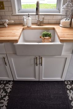 Ikea farm sink. Butcher block counter top. White cabinets and gold hardware.