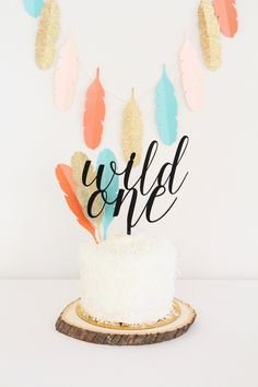 Wild One Tribal 1st Birthday Party | Custom Acrylic Cake Topper from Sweet Paper Shop |  Fringy Coconut Cake & Rustic Wood Base | DIY Paper Feather Garland & Cake Decoration | Read about it on our blog!