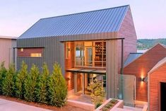 Love the way the metal wraps from the roof down the sides, as well as the abundance of natural light. The wood adds warmth. Great modern farmhouse.