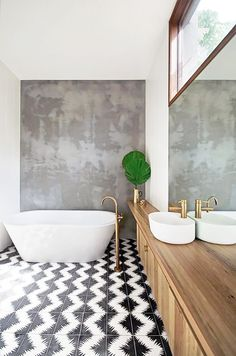 The mixture of black, white, concrete, wood and brass together creates a stylish whole in this bathroom