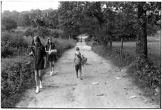 Children and a dog walking on a dirt road; two girls carrying books. 1972. Eastern Kentucky. Photo by William Gedney.