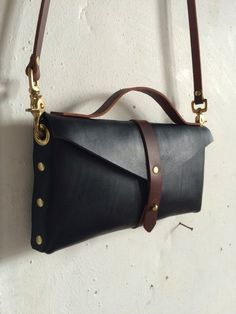 Simple and discreet bag with a removable carry strap and short handle for use as a clutch. Perfect for a night out or a day in the city. Measures 11X1.5X4.5 Constructed of vegetable tanned leather and all solid brass hardware, this bag is made to be durable and stylish for years to come.