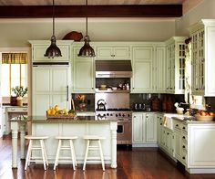 Comfort Is Key  Key to this kitchen's laid-back cottage look: simple lines, vintage designs, and breezy seafoam green cabinetry that reminds the homeowners of Depression Era glassware.    The center island mimics the look of an old wood farm table with substantial turned legs, while humble four-legged stools painted white lighten the look and provide practical perches for helpers and diners alike.