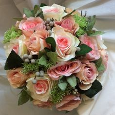 A large bridal bouquet of pink and apricot silk rose flowers