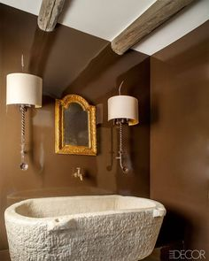 """""""They're all supposed to look like nothing happened and no one did anything,"""" Egan says of his traditional interiors. """"Except that now the toilets work and you've got Wi-Fi."""" A powder room's stone sink and brass faucet are antique, the circa-1730 giltwood mirror is Spanish, and the sconces are by Restoration Hardware."""