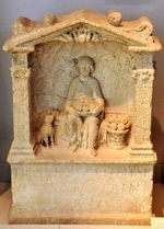 The Godess Nehalennia sitting on a throne in an apse between two columns, holding a basket of apples on her lap. Nearly always, there is a wolf dog at her side.