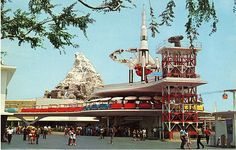 A Peek at Vintage Disneyland. | A single Skyway gondola glides past the loading platform for the PeopleMover and the Rocket Jets as the Matterhorn looms beyond.