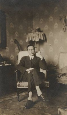 Photograph of Marcel Duchamp seated, smoking, in Katherine Dreier's apartment. 135 Central Park West, New York City