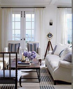 black and white stripes - black and white stripes in grid design on a carpet and striped accent pillows in a white room - Victoria Hagen via Atticmag