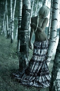 Blonde girl with braid in the forest. Mysterious