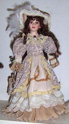 Victorian Porcelain Doll. Her hair is in ringlets & her dress is double layered with lace & ribbed edging at bottom of sleeves & skirt. She is wearing a faux pearl beaded necklace.
