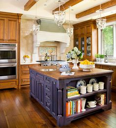 Kitchen Island Inspiration  When visualizing your new kitchen, try starting with an inspiration piece. A hand-painted vintage Italian ceramic bowl served as the inspiration for this kitchen's color scheme. The cobalt paint on the stately, furniture-like island pops against the rich wood tones. Built-in shelving on one end of the island houses cookbooks and dishes.