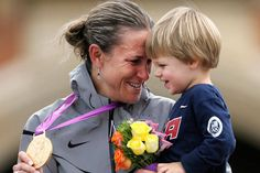Gold medalist Kristin Armstrong of the United States celebrates with her son, Lucas, after the women's individual time trial event