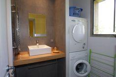 Salle de bain équipée avec machine à laver et sèche-linge.