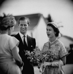 A woman greeting Queen Elizabeth II and Prince Philip with a smile and bouquet of flowers. Location: Jamaica Date taken: November 1953 Photographer: Cornell Capa