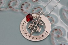 This necklace features:  1 inch sterling silver washer  sterling RN charm  swarovski crystal heart      Perfect for a nurse!    Comes with a