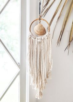 Total beach shack vibes for all you lovers of an endless summer! This gorgeous wall hanging is made with a beautiful sea shell, collected on the beaches of the East Coast, at the center of a rattan ho