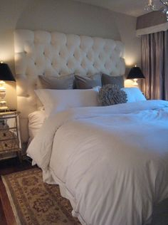 Bed idea! Meredith Heron Designs    chic bedroom design with custom made tall white tufted headboard, mirrored nightstands, crisp white bedding, gray velvet pillows, alabaster lamps with black silk shades, gray silk cornice box, gray silk drapes, oriental rug and round gray silk flower pillow. soft gray walls paint color. white gray bedroom colors.