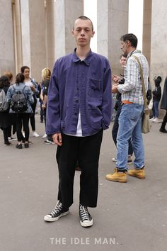 Men's Street Style | Layered Look - At Paris Fashion Week SS17 this guy is loving the layered look and so are we. Pair a plain white tee with baggy black trousers and layer with a denim blue shirt, buttoned up at the top. We think these black Chuck Taylor All-Star Hi-Top plimsolls really make this look. | Shop the look at The Idle Man.