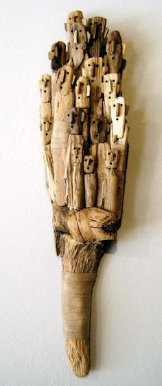 Community of faces wood sculpture from a single piece of gnarled wood. Artist: Marc Bourlier