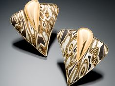 James Binnion has an interesting collection of jewelry that uses Mokume-gane. Sometimes, to increase the wood grain effect, Binnion will carve out sections to add to the texture.