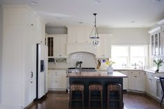 Classic white kitchen with butcher block island and rattan stools
