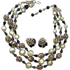Lovely vintage set circa 1965 by Deauville, triple strand necklace with matching earrings with caged beads. The necklace is adjustable from 15 - 17