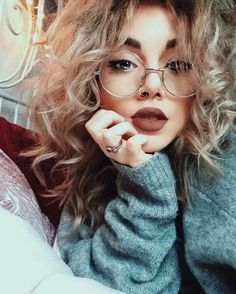 curly hair, fashionable glasses, pouty lips