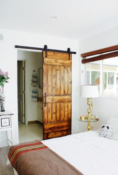 A barn door on sliding sections off the master bedroom from the bath—and brings character to the space. Bedroom Barn Door, Beach House Bedroom, Home Decor Bedroom, Living Room Decor, Diy Home Decor, Living Spaces, Bedroom Sets, Master Bedroom, Bedrooms