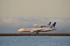 San Francisco Intl Airport (SFO) Runway 28L UAL 777 preparing to takeoff, and UAL Airbus landing on 28R