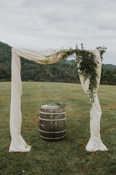 Wedding arch draped in white & rustic barrel accent | Hartman Outdoor Photography