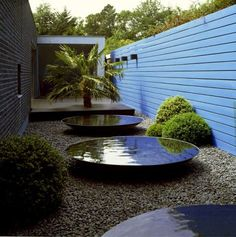 Shallow, dark, dishes of water can refect a lot of light into the garden (and sometimes through the house windows). The repetition is what makes this design. A single dish would need supporting elements.