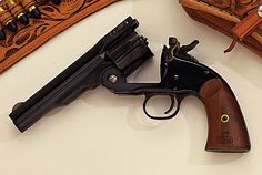 """Navy Arms 1875 Schofield The Smith & Wesson Schofield wasn't as popular as the Colt back in 1875, but the clone became popular after one was featured in the Clint Eastwood movie """"Unforgiven."""" The gun loads by swinging down the hinged barrel, which activates the ejector rod that, in turn, pops out all six shells at once. New Cowboy Guns Of The Old West -"""