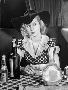 <b>Caption from LIFE.</b> In Giono's little speakeasy in the West Forties, Kitty Foyle sits between a bottle of Scotch and a decanter of water, turning a little glass stirring rod around in her hand. Wyn is lost to her forever, engaged to marry the kind of Main Line girl she always knew he was destined to marry. In the novel, Kitty goes on to success but finds no one to fill Wyn's place in her heart. Here LIFE leaves Kitty in the hope that RKO and Ginger Rogers can find happy ending for…