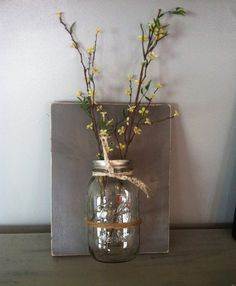 This beautiful mason jar wall vase is made from a piece of reclaimed pine that has been stained a a weathered gray and then sanded for a perfect rustic distressed look! The large mason jar makes a perfect a vase and beautiful farmhouse wall decor! The board measures 9.25 x 11.5. Great for storage in kitchen or bathroom. Awesome housewarming gift! Please note that this listing does not include the flowers.