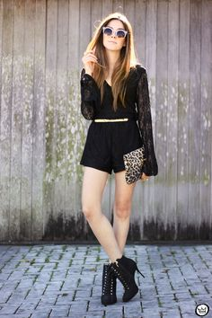 Casual chic outfit wearing a black lace romper with long sleeves. Also wearing leopard printed clutch and high heels.