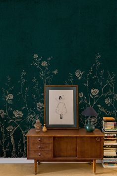 A wallpaper mural scene featuring long-tailed birds perching on trailing branches of wild floral plants while butterflies flutter by.