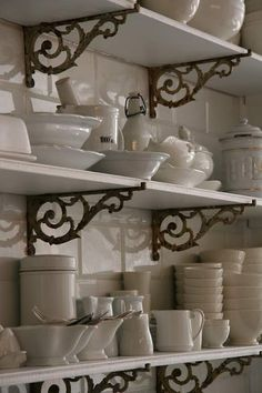 Open shelving in the kitchen, displaying a huge collection of white dishes. Vintage brass brackets stand out on the white tiled wall.