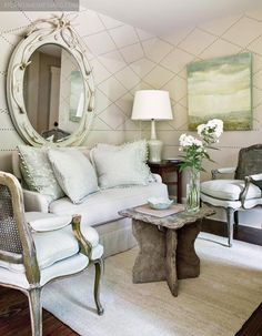 A sitting area decorated in soft colors ... great mix of antique & rustic furniture.
