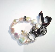Fresh Coin Bracelet . This Bracelet is made up of coin fresh water pearls with a black diamond spacer bead tucked away , a fleur de Li button clasp and leather