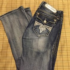 """Rock Revival Sz 29 Sora Boot cut jeans Medium wash RR denim. Excellent condition. Size 29 Sora Boot cut. Hemmed to a little over 30"""" inseam by seamstress at the Buckle store I purchased them at. No distressing. Good for dressing up. A few stones missing off back pockets but does not distract from the overall look. Very gently worn. Do have some stretch. Rock Revival Jeans Boot Cut"""