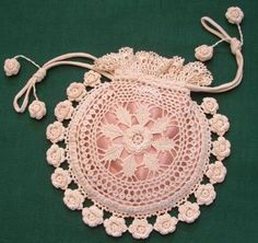 An Evening bag in Irish Crochet, The roses have beads for   accent and are double sided around the edging, so they are   just as beautiful on one side as the other. The purse body   measures 7 inches across, not counting the rose edging. Draw   string closure with stuffed roses for accent. The design is done in   size 30 thread.